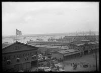 View of the Hudson River piers and ships on the river for the Dewey Naval Parade, New York City, September 29, 1899. Spectators on the roofs of the piers.