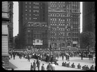 Crowd watching baseball scores being posted on the Sun Building, New York City, 1914. Base of the Tribune Building also visible.