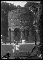 Unidentified little girls posing in front of the Newport Tower, Touro Park, Newport, Rhode Island, undated (ca. 1895-1905). Emulsion damage.
