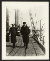 Two unidentified men walking on the deck of a vessel, undated [circa 1900-1910].