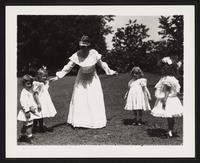 Unidentified woman and children playing an outdoor game, undated [circa 1900-1910].