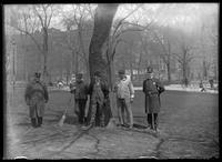 Unidentified man in a suit posing with two police officers and two park custodians in an unidentified park, New York City, 1905.