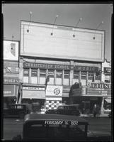 125th Street between Seventh Avenue and Lenox Avenue, New York City, February 16, 1932: 1 empty billboard.  Also storefronts of Tip Top Shoes Shop, Toby's Men's Shop, Christensen School of Music, Orient Photo Plays.