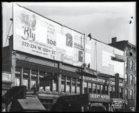 125th Street between Seventh Avenue and Lenox Avenue, New York City, January 1922: Brooklyn Shoe ['Blyn Shoe'], Brunswick Phonographs and Records (both in the process of being put up or taken down). Also storefronts of Ideal Shoe Shop, Christensen School