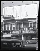 125th Street between Seventh Avenue and Lenox Avenue, New York City, May 29, 1934: 1 empty billboard, Cadillac Cars (partial). Also storefronts of Cameo Men's Shop, Orient Restaurant, Orient Photo Plays.