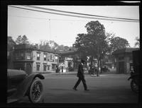 Flsushing: unidentified intersection, man crossing street in foreground, undated.