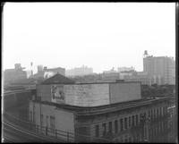 El tracks above Eighth Avenue and West 110th Street, looking southwest, New York City, circa 1921: Lion Brewery (far distance), Live Leather Belt and several blank billboards.