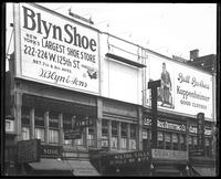 125th Street between Seventh Avenue and Lenox Avenue, New York City, May 1920: Brooklyn Shoe, Brill Brothers (Kuppenheimer Clothes). Also storefronts of Lenox Shoe Shop, Christensen School, Orient Movies, Leight Brothers Outfitting Company.