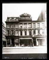 Broadway at the corner of 8th Street, New York City, showing Fredericks Photograph, Portrait & Art Gallery; Mosler Bowen & Co., safes; Cafrees Artificial Limbs; and John Barnett Morocco Cases. Copy negative of an 1895 photograph of an unknown photographer