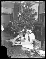 William Gray Hassler (boy) and unidentified girl seated under a Christmas tree, reading a book together, undated (ca. 1913-1914). William holds a stuffed chimpanzee.