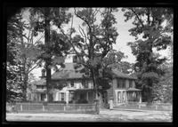 Manhasset / Roslyn / Little Neck / Douglaston / Alley Road, Long Island: [unidentified large wood house with multiple covered porches and entries, behind a fence, surrounded by trees, undated.]