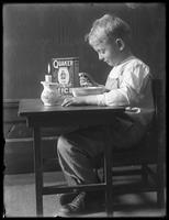 William Gray Hassler (little boy) seated at a small table eating a bowl of Quaker puffed rice cereal, ca. 1912.