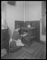 Miss Bates taking bread from the oven, undated. Location unidentified.