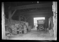 Car and tractors in unidentified garage, undated.