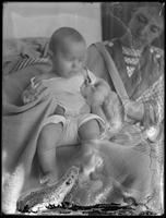 Lundy baby and woman, October 6, 1912. Blurry, with emulsion damage.