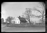 Unidentified Dutch Colonial house in good repair, behind new fence, undated.