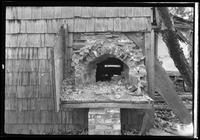 Ruined brick wall oven seen from the exterior of an unidentified house, undated.