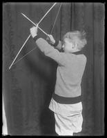 3/4 length studio portrait shot of William Gray Hassler posing with bow and wooden arrow, undated.