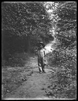 William Gray Hassler (little boy) in straw hat and overalls, carrying fishing pole (?) and basket, standing on a path in the woods, August 20, 1911. Facing camera.