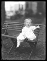 Unidentified toddler posed on a folding bench, undated (ca. 1913).