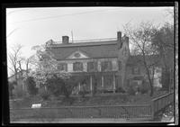 Unidentified Dutch Colonial house with fence, flowering dogwood tree, undated. For sale sign on front lawn.