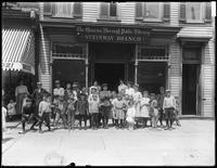 Group portrait of children in front of the Steinway branch of the Queens Borough Public Library, ca. 1910.