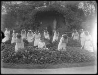 Graduating class of girls from the Roman Catholic Orphan Asylum in the flower garden, in front of the Virgin Mary's grotto, 1912.