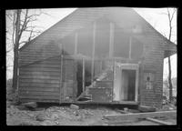 Side view of unidentified wood-shake saltbox house with wall torn open, undated.