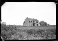 Shell of an unidentified saltbox house surrounded by overgrown fields, undated.