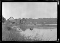 Huntington, Long Island: [unidentified bay or inlet, with old wood-shake barn or water mill, possibly used as a clam shack, and larger industrial building, undated. Houses in distance.]