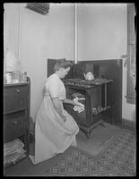 Ethel Gray Magaw Hassler taking bread from the oven, undated. Location unidentified.