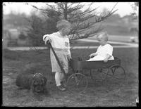 Unidentified toddler and infant posed with a wagon and a dog, ca. April 1915 [?].
