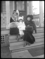 Elizabeth and Margaret Creighton and an unidentified little girl posed on front porch steps in fur-trimmed coats, hats, and muffs, Irvington, N.Y., undated.