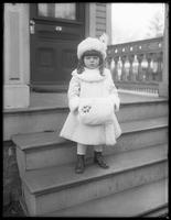 Creighton little girl in coat and muff posed on front porch steps, Irvington, N.Y., undated.