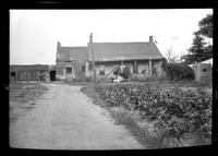 Front view of unidentified old farmhouse with a planted field in the foreground, undated.