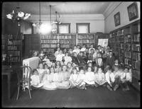 Group portrait of children in the reading room of an unidentified branch of the Queens Borough Public Library, ca. 1910.