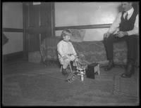 Dan Seymour watching his son playing with teddy bear and toy piano, undated.