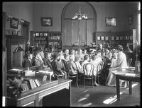 Children listen to a woman (story time?) in the reading room of an unidentified branch of the Queens Borough Public Library, ca. 1910.
