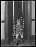 Seymour boy posed on an indoor swing hung in a doorway, undated.