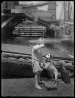 Barefoot boy [William Gray Hassler?] plays with dog on the shore of a river or lake, ca. 1910.