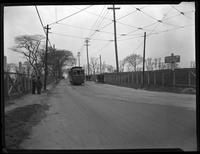 Bend in an unidentified road with automobiles and trolley, and sign 'To North Beach,' Queens, undated (ca. 1920).