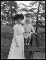 Portrait of Ethel Gray Magaw Hassler and her son William Gray Hassler, posed beside a rustic wood fence, ca. 1911.