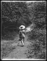 William Gray Hassler (little boy) in straw hat and overalls, carrying fishing pole (?) and basket, walking down a path in the woods alone, August 20, 1911. Back to camera.