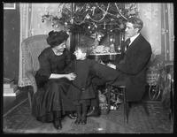 Dan Seymour and family (wife and child) in informal pose, seated beneath Christmas tree, Christmas 1912.
