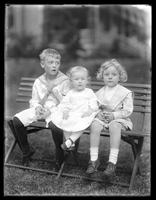 William Gray Hassler (boy) and two other children posed on a folding bench, undated (ca. 1913).