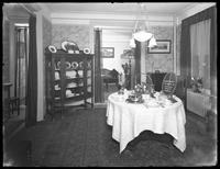 Dining room and living room of a model apartment, New York City, May 6, 1915. Photographed for the United Electric Light & Power Company.