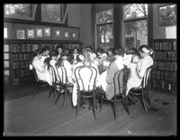 Group of unidentified girls sewing around a table in the reading room of a public library in College Point, Queens, undated.