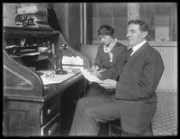 Aaron Bers and unidentified woman [secretary?], at a desk in 10 1/2 Debrosses Street, New York City, undated.