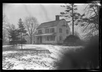 Unidentified Dutch Revival-style house in winter with snow, undated. Frame partially obscured.