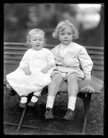 Small child and toddler posed together on a garden bench, undated (ca. 1913). Motion blur.